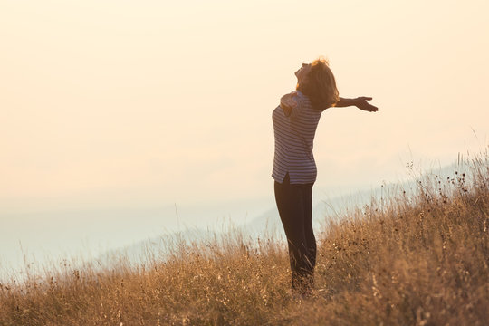 Young woman standing on mountain and having fun on grass field
