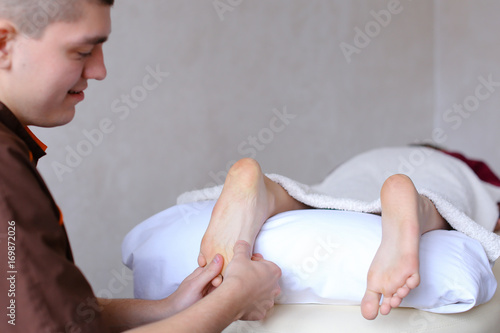male doctor massages feet of young girl who lies on couch in bri