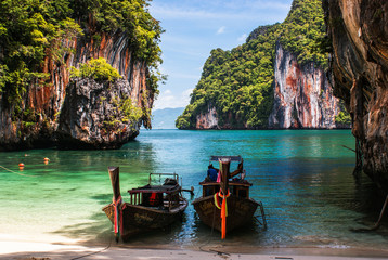 Longtail boat on the shore of a tropical island, surrounded by cliffs . Krabi Thailand