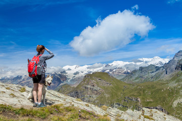 donna che guarda panorama in montagna con cane