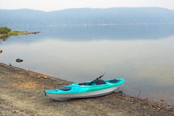 幻想的な霞のかかった湖の浜に置かれたカヤック