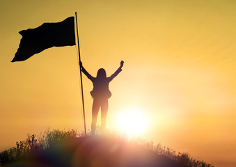 High achievement, silhouettes of the girl, flag of victory on the top of the mountain, hands up. A man on top of a mountain. Conceptual design. Against the dramatic sky with clouds at sunset.