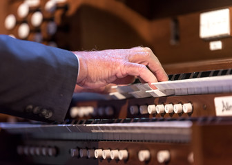 A close up image of a man playing organ