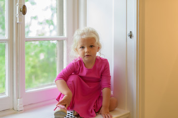 Pretty little blond girl sitting on window seat in old house