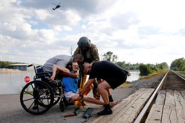 Rescue personnel help Hersey Kirk into a restraint as a rescue helicopter hovers in the distance after she was rescued from her home flooded by Tropical Storm Harvey in Rose City