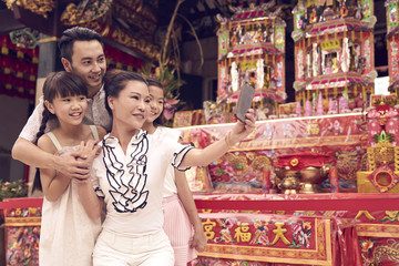 Family of four taking a selfie in a temple