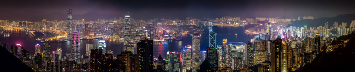 Night light panoramic cityscape of Central District and Kowloon, Hong Kong. Scenery aerial view from the peak mountain.