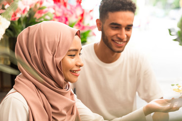 Young muslim couple smiling while admiring flowers
