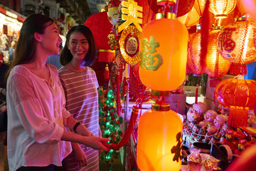 Two girlfriends shopping for decorations in Chinatown
