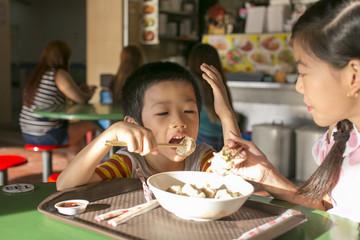 Siblings eating in a hawker