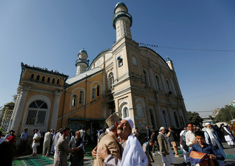 Afghans greet each other outside the Shah-e Doh Shamshira Mosque, on the first day of the Eid al-Adha, in Kabul, Afghanistan