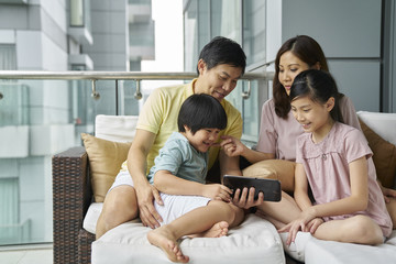 Family of four bonding on the balcony over an electronic tablet