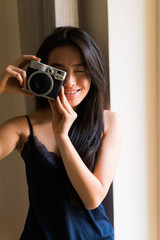 Young woman taking picture with a vintage camera