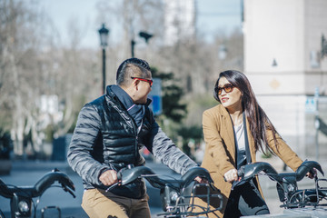 Chinese couple riding a bicycle at Plaza Ramales , Madrid