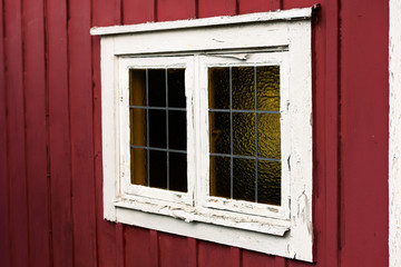 Old window on a red cottage with white window frame. The white frame is flaking and in need of attention. Lead mullions or glazing bars on the glass window.