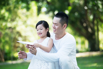 Young happy Asian father and daughter spending time together at the park.