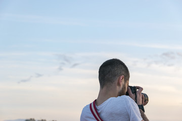 Professional photographer taking outdoor portraits of sunset with prime professional lens