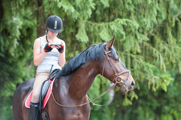 Chestnut horse with teenage girl with smartphone sitting on it