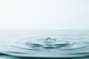 Water drop and splash on water surface on blue background