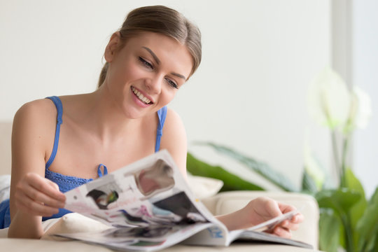 Smiling carefree young woman lying on sofa in living room at home flipping magazine pages. Relaxed happy lady reviewing fashion season latest trends, examining, choosing goods in supermarket catalog