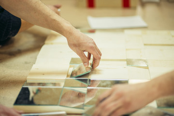 Carpenters workshop with a craftsman building a display case from wood and glass