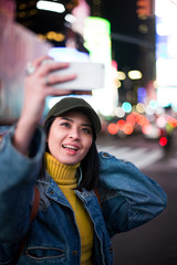 Female tourist taking a smiling selfie in Times Sqaure