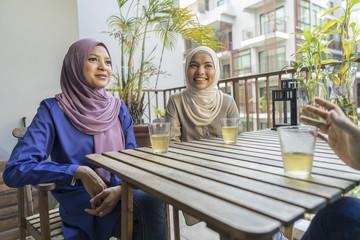 3 Ladies having a conversation over tea.