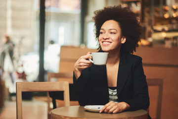 Businesswoman taking break and drinking coffee in cafe