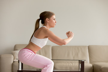 Attractive young woman in sportswear doing sit-ups in living room, training legs, trying to form perfect butt shape, squatting at home. Fitness at hotel, morning exercises, female physical activity