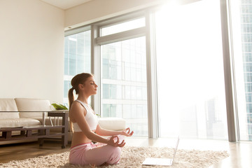 Attractive young woman wearing comfortable sportswear relaxing, meditating on living room carpet. Calm lady sitting on floor in lotus position in front of laptop, listening spiritual practices lessons