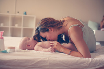 Young mother playing with her baby boy in bed. Mother enjoying in free time with her little cute baby.