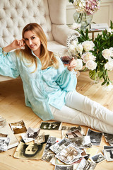 Young sexy beautiful blonde woman sits on the floor looks  family album with photos of memories of friend, a bright room with flower,sofa,cozy family hearth, model wear blue blouse and white trousers.
