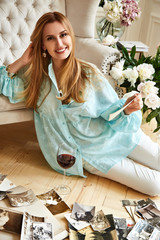 Sexy beautiful blonde woman sits on the floor looks family album with photos of memories of friend,drink red wine bright room flower,sofa,cozy family hearth, model wear blue blouse and white trousers.