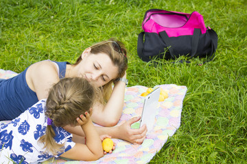 mother and daughter in the Park and look at the tablet and eat the peaches