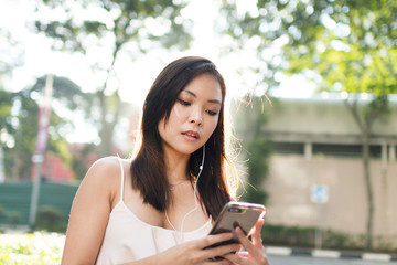 Pretty Asian Girl with Phone In The Street