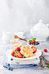 Breakfast with scotch pancakes in flower form, berries and honey on light wooden table. Healthy food concept with copy space.