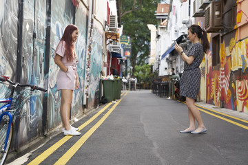 Girlfriends taking photos beside a wall filled with graffiti in Haji Lane, Singapore