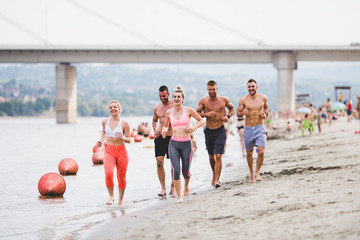 Group of young attractive people fitness workout. They having fun and running at beach.