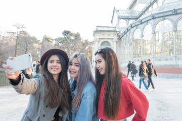 Happy Friends taking selfie in Retiro Park Madrid