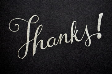THANKS hand lettered in silver pen on black card