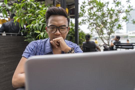 A Filipino Man Thinking While Staring At His Laptop.