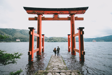 Back view of a young hipster couple at Itsukushima Shrine, Japan