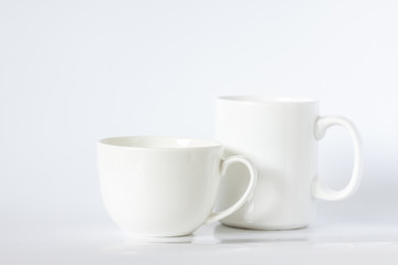 Two white porcelain mugs, different size and design,  dishes mock up
