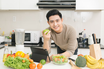 Handsome young man eating a healthy fresh green apple in kitchen at home
