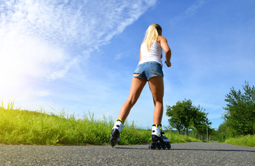 Teenage girl on roller skates at summer. Inline skating on the road.