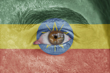 Human face and eye painted with flag of Ethiopia