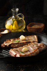 Grilled pork ribs with rosemary, spices and garlic in a frying pan grill