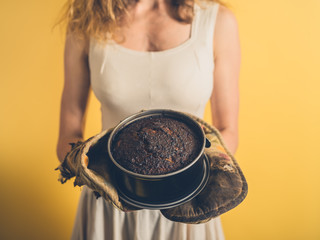 Young woman holding a burnt cake
