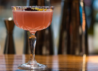 Pink cocktail garnished with flowers in Margarita glass. Alcoholic drink in tall glass on wooden counter of bar