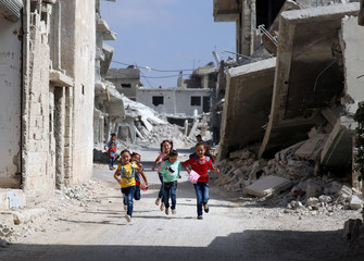 Children run along a damaged street as they celebrate the first day of the Muslim holiday of Eid al-Adha at a rebel-held area in Deraa